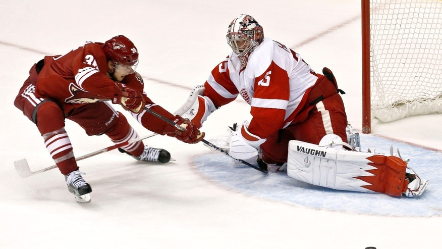 Phoenix Coyotes' Rob Klinkhammer, left, gets his shot kicked away by Detroit Red Wings' Jimmy Howard in the third period during an NHL hockey game on Thursday, April 4, 2013, in Glendale, Ariz.  The Coyotes defeated the Red Wings 4-2. (AP Photo/Ross D. Franklin)
