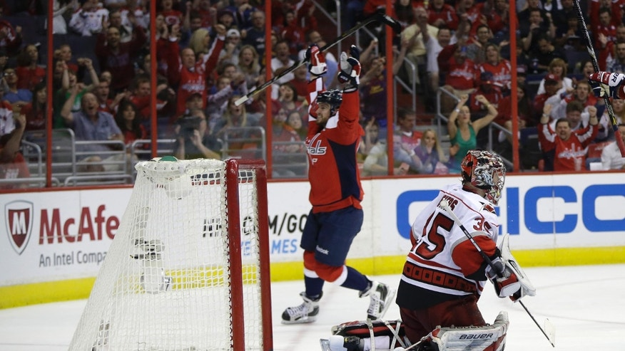 Carolina Hurricanes goalie Justin Peters, right, is beaten for a goal by Washington Capitals defenseman Mike Green during the second period of an NHL hockey game on Thursday, April 11, 2013, in Washington. (AP Photo/Evan Vucci)