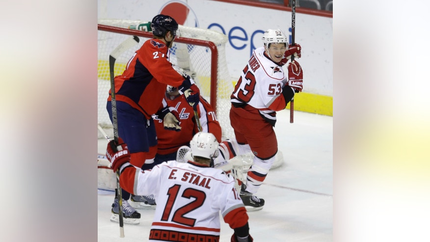 Carolina Hurricanes center Jeff Skinner, right, smiles at teammate Eric Staal, third from left, after scoring past Washington Capitals defenseman Karl Alzner, left, and goalie Braden Holtby during the first period of an NHL hockey game on Thursday, April 11, 2013, in Washington. (AP Photo/Evan Vucci)