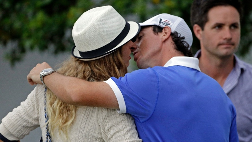 Rory McIlroy, of Northern Ireland, kisses tennis player Caroline Wozniacki after his first round of the Masters golf tournament Thursday, April 11, 2013, in Augusta, Ga. (AP Photo/David Goldman)