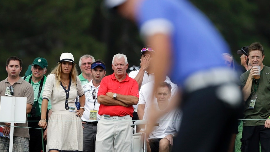 Tennis player Caroline Wozniacki watches Rory McIlroy, of Northern Ireland with his father Gerry, right, during the first round of the Masters golf tournament Thursday, April 11, 2013, in Augusta, Ga. (AP Photo/David Goldman)
