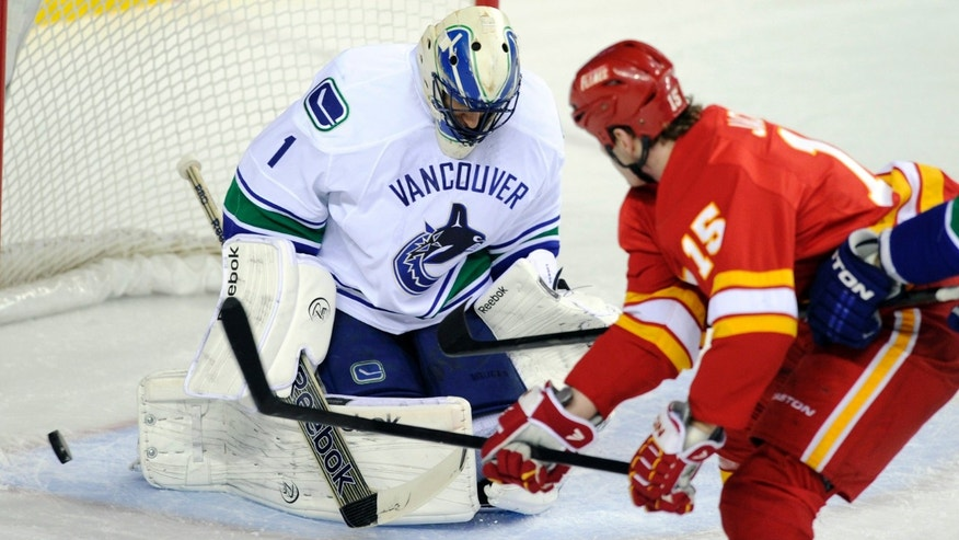 Vancouver Canucks goalie Roberto Luongo makes a save against Calgary Flames' Tim Jackman during the first period of an NHL hockey game in Calgary, Alberta, Wednesday, April 10, 2013. (AP Photo/The Canadian Press, Larry MacDougal)
