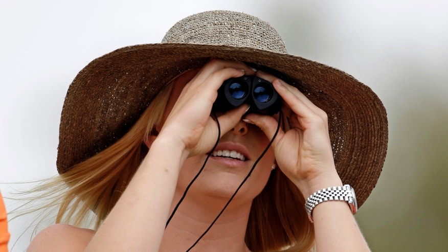 Skier Lindsey Vonn tries a pair binoculars to watchTiger Woods during the first round of the Masters golf tournament Thursday, April 11, 2013, in Augusta, Ga. (AP Photo/Darron Cummings)