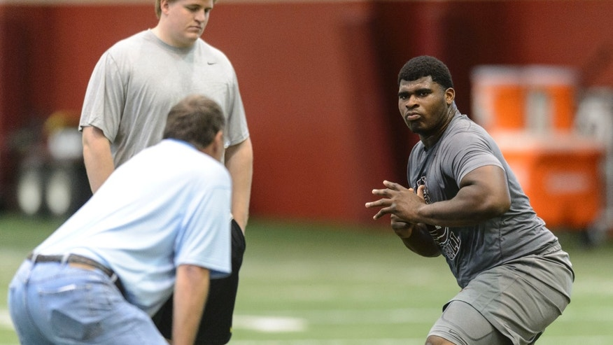 Former Alabama lineman D.J. Fluker, right, works for an NFL official as former Alabama center Barrett Jones, rear left, watches during Alabama's second pro day for NFL scouts, Thursday, April 11, 2013, in Tuscaloosa, Ala. (AP Photo/AL.com, Vasha Hunt) MAGS OUT