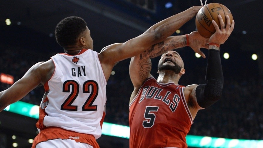Toronto Raptors forward Rudy Gay (22) defends against Chicago Bulls forward Carlos Boozer during the first half of an NBA basketball game action in Toronto on Friday, April 12, 2013. (AP Photo/The Canadian Press, Frank Gunn)