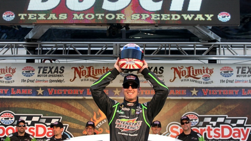 Kyle Busch holds up the pole-sitter helmet trophy after qualifying for the NASCAR Sprint Cup Series NRA 500 auto race at Texas Motor Speedway, Friday, April 12, 2013, in Fort Worth, Texas. Busch earned the position with a new track record. (AP Photo/Tim Sharp)