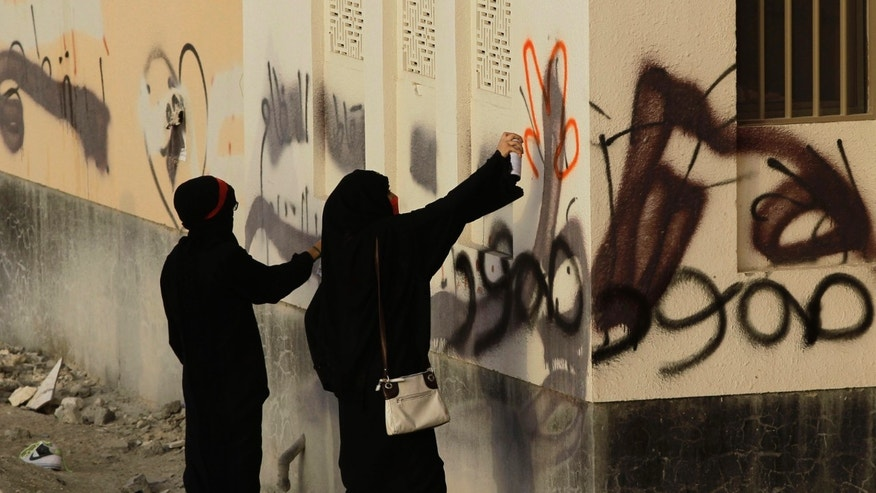 "Bahraini women spray anti-government graffiti during a march in A'ali, Bahrain, on  Friday, April 12, 2013. Old political graffiti includes ""steadfast."" Thousands of anti-government demonstrators in Bahrain have joined a march that included breakaway protests against the scheduled Formula One race later this month. (AP Photo/Hasan Jamali)"