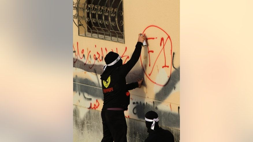 "A Bahraini anti-government protester sprays graffiti opposing the upcoming Formula One Bahrain Grand Prix during a march in A'ali, Bahrain, on  Friday, April 12, 2013. It reads: ""no to Formula"" next to F1 being crossed out. Thousands of anti-government demonstrators in Bahrain have joined a march that included breakaway protests against the scheduled Formula One race later this month. (AP Photo/Hasan Jamali)"