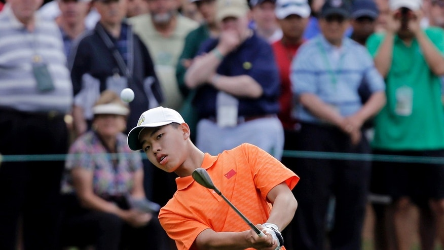 Amateur Guan Tianlang, of China, chips to the first green during the second round of the Masters golf tournament Friday, April 12, 2013, in Augusta, Ga. (AP Photo/David J. Phillip)