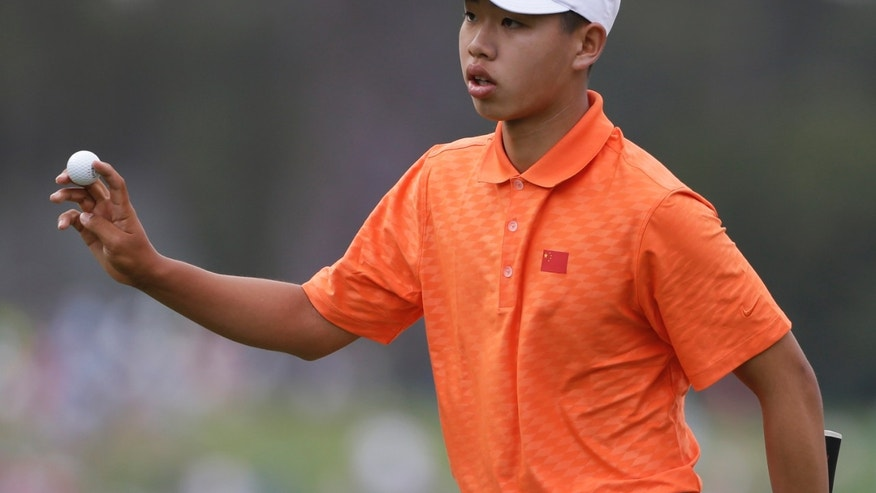 Amateur Guan Tianlang, of China, hold up his ball after putting on the first green during the second round of the Masters golf tournament Friday, April 12, 2013, in Augusta, Ga. (AP Photo/Darron Cummings)