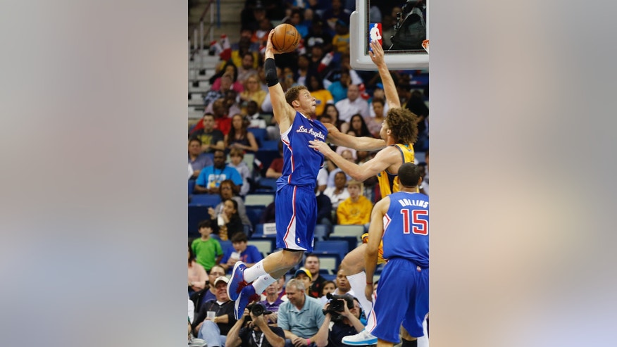 Los Angeles Clippers forward Blake Griffin, left, goes to the basket over New Orleans Hornets center Robin Lopez during the first half of an NBA basketball game,Friday, April 12, 2013, in New Orleans. (AP Photo/Bill Haber)