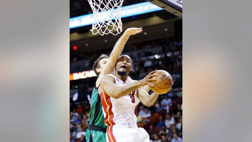 Miami Heat forward Rashard Lewis (9) goes up for a shot against Boston Celtics forward Shavlik Randolph during the first half of an NBA basketball game, Friday, April 12, 2013, in Miami. (AP Photo/Wilfredo Lee)