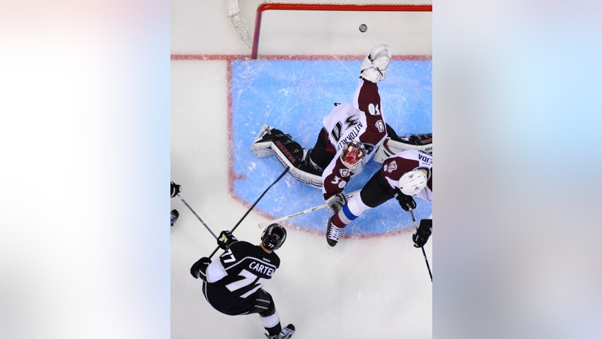 Los Angeles Kings center Jeff Carter, below, shoots but is unable to score on Colorado Avalanche goalie Sami Aittokallio, top, of Finland, as defenseman Jan Hejda, of the Czech Republic, watches during the first period of their NHL hockey game, Thursday, April 11, 2013, in Los Angeles. (AP Photo/Mark J. Terrill)