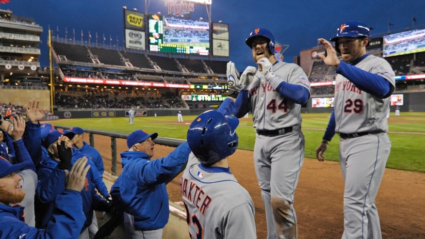 New York Mets' John Buck (44) is welcomed at the dugout after his grand slam off Minnesota Twins pitcher Pedro Hernandez in the second inning of a baseball game on Friday, April 12, 2013, in Minneapolis.  Mets' Ike Davis, right, looks on. (AP Photo/Jim Mone)