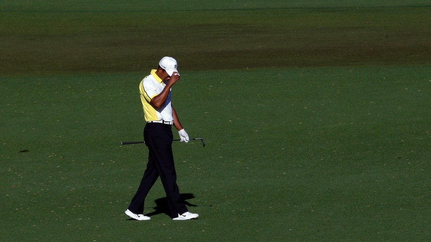 Tiger Woods reacts after his fairway shot on the 15th hole hit the pin and rolled into the water during the second round of the Masters golf tournament Friday, April 12, 2013, in Augusta, Ga. (AP Photo/Charlie Riedel)