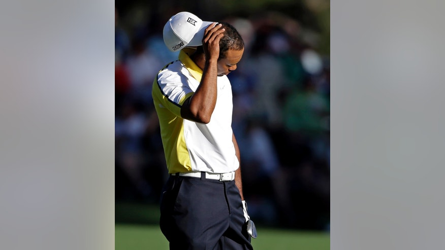 Tiger Woods reacts after his fairway shot on the 15th hole hit the pin and rolled into the water during the second round of the Masters golf tournament Friday, April 12, 2013, in Augusta, Ga. (AP Photo/Darron Cummings)