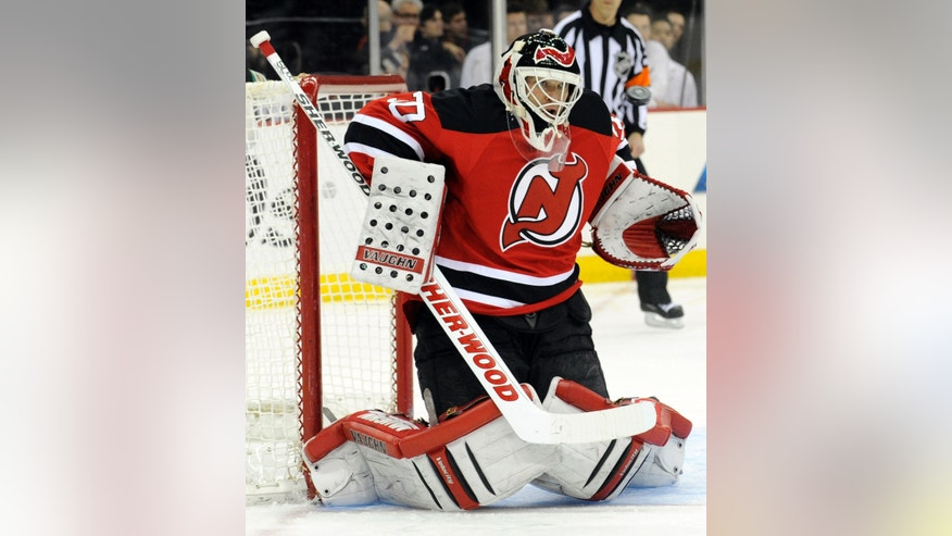 New Jersey Devils goaltender Martin Brodeur eyes the puck during the first period of an NHL hockey game against the Ottawa Senators,  Friday, April 12, 2013, in Newark, N.J. (AP Photo/Bill Kostroun)