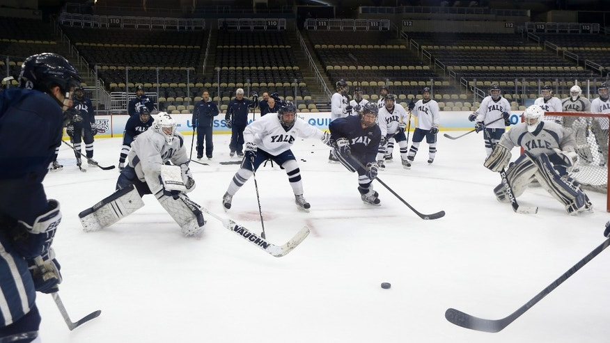 Yale players work on a drill between goaltenders Jeff Malcolm, left, and Nick Maricic, right, during NCAA college hockey practice at the Frozen Four on Friday, April 12, 2013, in Pittsburgh. Yale takes on Quinnipiac on the championship game on Saturday. (AP Photo/Keith Srakocic)
