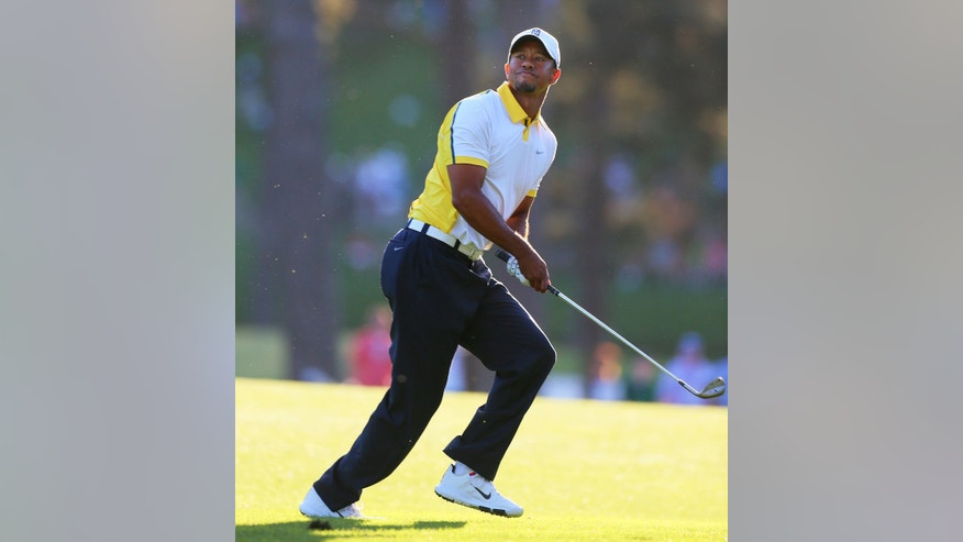 Golfer Tiger Woods reacts to his recovery shot from off the fairway over the trees to the 17th green during the second round in the Masters golf tournament on Friday, April 12, 2013, in Augusta, Ga. (AP Photo/Atlanta Journal-Constitution, Curtis Compton) MARIETTA DAILY OUT&#x3b; GWINNETT DAILY POST OUT&#x3b; LOCAL TV OUT&#x3b; WXIA-TV OUT&#x3b; WGCL-TV OUT.