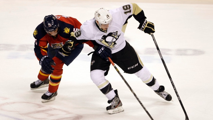 Pittsburgh Penguins' Beau Bennett (19) and Florida Panthers' Drew Shore (15) fight for the puck during the second period of an NHL hockey game on Saturday, April 13, 2013, in Sunrise, Fla. (AP Photo/Lynne Sladky)