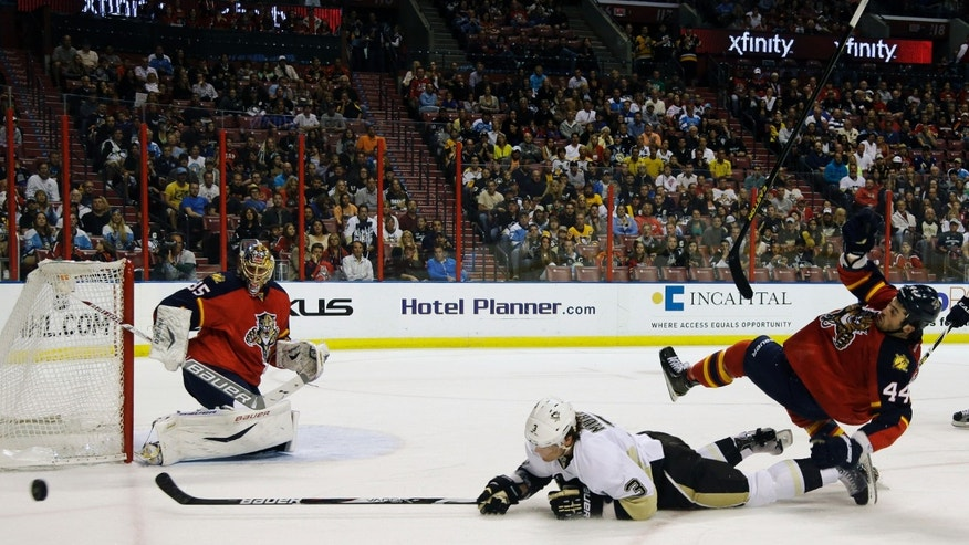 Pittsburgh Penguins' Douglas Murray (3) attempts a shot on a goal as Florida Panthers' Erik Gudbranson (44) loses his stick during the first period of an NHL hockey game, Saturday, April 13, 2013, in Sunrise, Fla. At left is Florida Panthers goalie Jacob Markstrom (35). (AP Photo/Lynne Sladky)