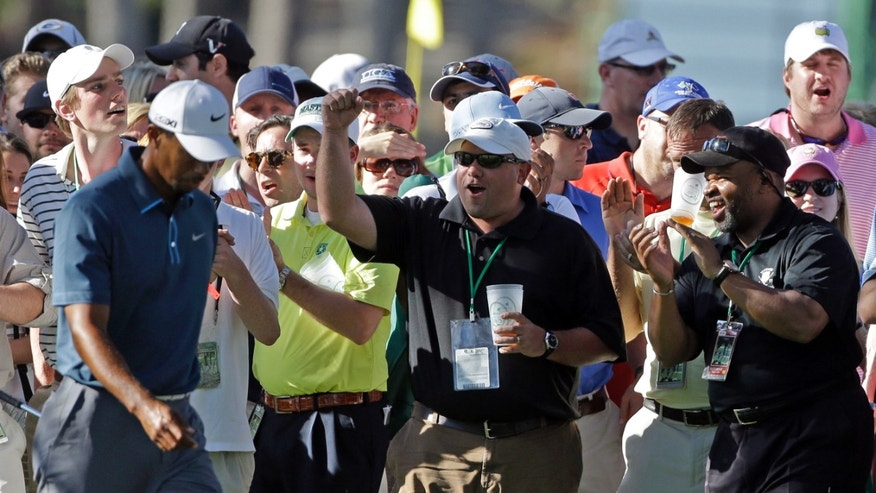 Tiger Woods is cheered by spectators as he walks up the 17th fairway during the third round of the Masters golf tournament Saturday, April 13, 2013, in Augusta, Ga. (AP Photo/David Goldman)