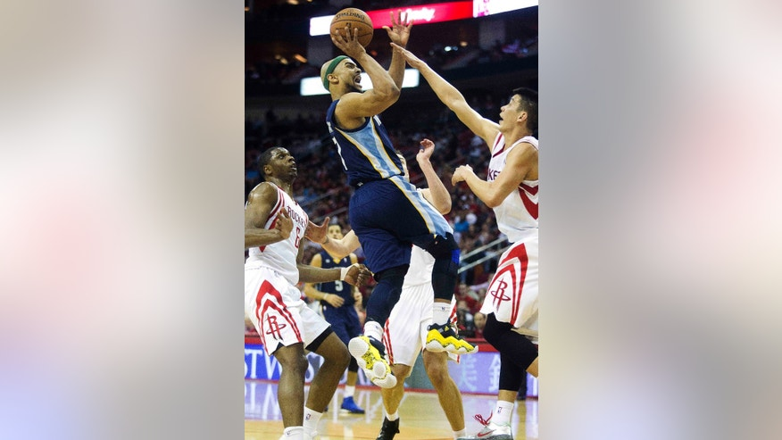 Memphis Grizzlies guard Jerryd Bayless, center, shoots over Houston Rockets guard Jeremy Lin, right, and forward Terrence Jones (6) during the first half of an NBA basketball game on Friday, April 12,  2013, in Houston. (AP Photo/Patric Schneider)