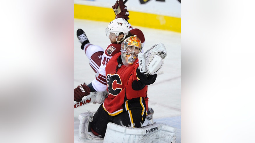 Calgary Flames goalie Joey MacDonald, right, makes a save despite being bumped by Phoenix Coyotes' Alexandre Bolduc during second-period NHL hockey game action in Calgary, Alberta, Friday, April 12, 2013. (AP Photo/The Canadian Press, Larry MacDougal)