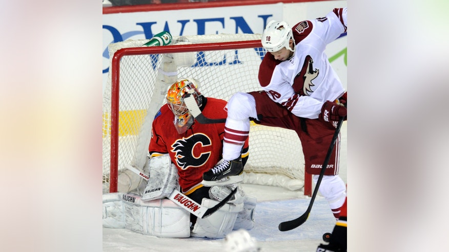 Phoenix Coyotes' David Moss, right, screens a shot on Calgary Flames goalie Joey MacDonald during the first period of an NHL hockey game in Calgary, Alberta, Friday, April 12, 2013. (AP Photo/The Canadian Press, Larry MacDougal)