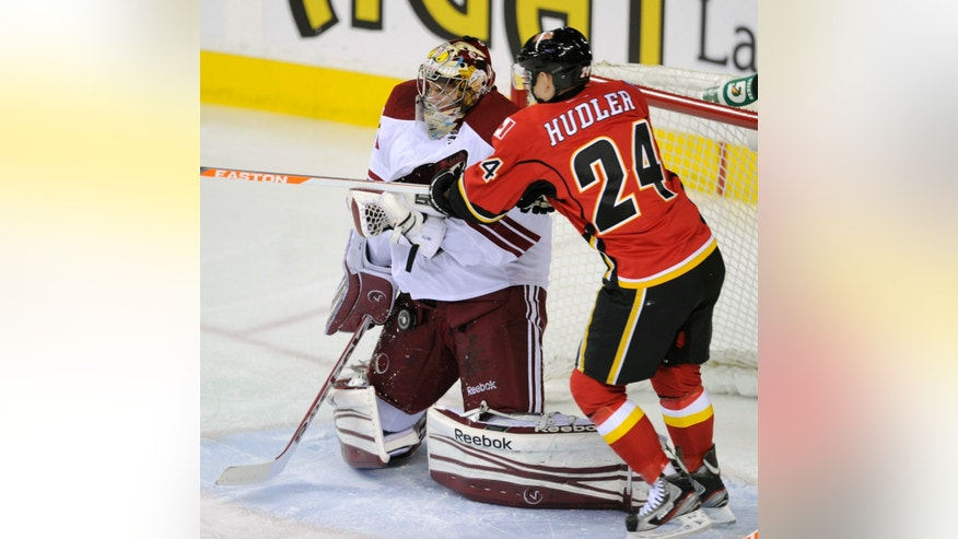 Phoenix Coyotes goalie Mike Smith, left, makes a save as Calgary Flames' Jiri Hudler, from Czech Republic, looks for the puck during first period of an NHL hockey game in Calgary, Alberta, Friday, April 12, 2013. (AP Photo/The Canadian Press, Larry MacDougal)
