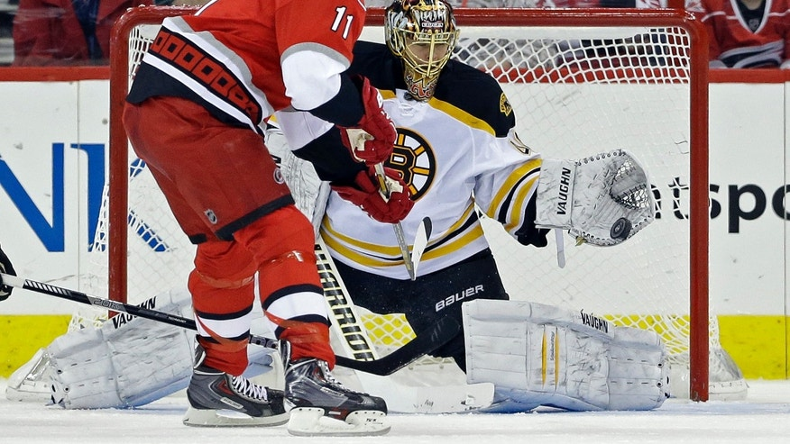 Carolina Hurricanes' Jordan Staal (11) is blocked by Boston Bruins Tuukka Rask, of Finland, during the first period of an NHL hockey game in Raleigh, N.C., Saturday, April 13, 2013. (AP Photo/Gerry Broome)