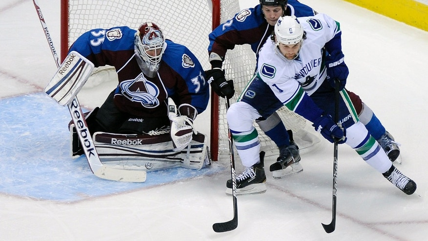 Colorado Avalanche goalie Jean-Sebastien Giguere (35) and Colorado defenseman Matt Hunwick, top, defend against Vancouver Canucks right wing Zack Kassian (1) in the first period of an NHL hockey game on Saturday, April 13, 2013, in Denver. (AP Photo/Chris Schneider)