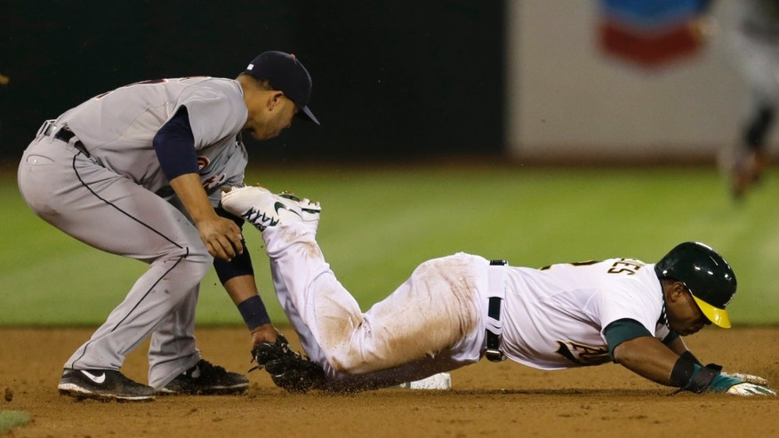 Oakland Athletics' Yoenis Cespedes, right, is tagged out by Detroit Tigers shortstop Jhonny Peralta in the eighth inning of a baseball game Friday, April 12, 2013, in Oakland, Calif. (AP Photo/Ben Margot)