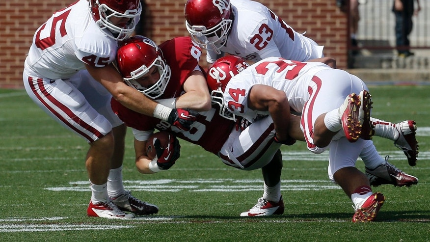 Oklahoma tight end Sam Grant (81) is tackled by defenders Caleb Gastelum (45), Kass Everett (23) and Daniel Brooks (34) during the annual Oklahoma spring intra-squad NCAA college football game in Norman, Okla., Saturday, April 13, 2013. (AP Photo/Sue Ogrocki)