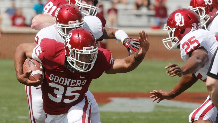 Oklahoma running back Terence Olds (35) runs past defender Aaron Franklin (25) during the Oklahoma spring intra-squad NCAA college football game in Norman, Okla., Saturday, April 13, 2013. (AP Photo/Sue Ogrocki)