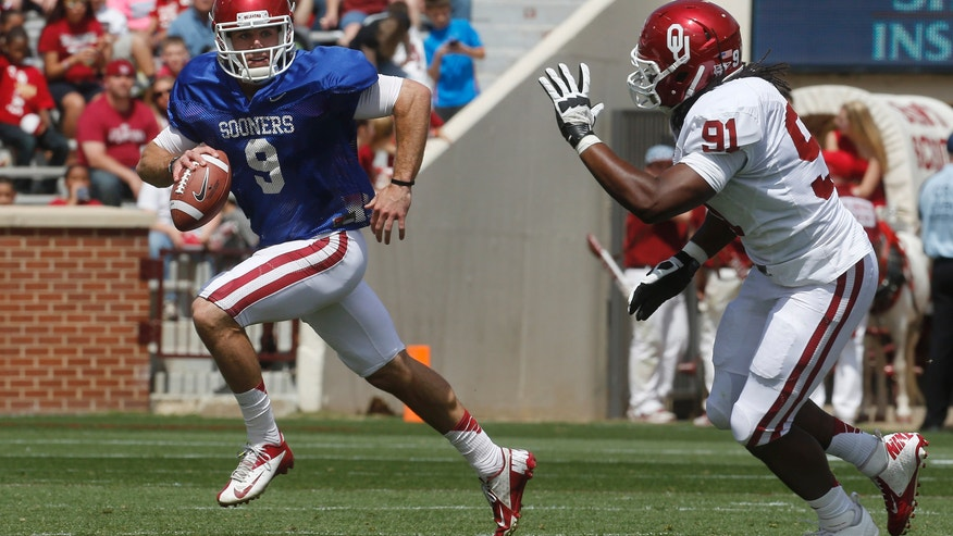 Oklahoma quarterback Trevor Knight (9) is chased by defender Charles Tapper (91) during the annual Oklahoma spring intra-squad NCAA college football game in Norman, Okla., Saturday, April 13, 2013. (AP Photo/Sue Ogrocki)
