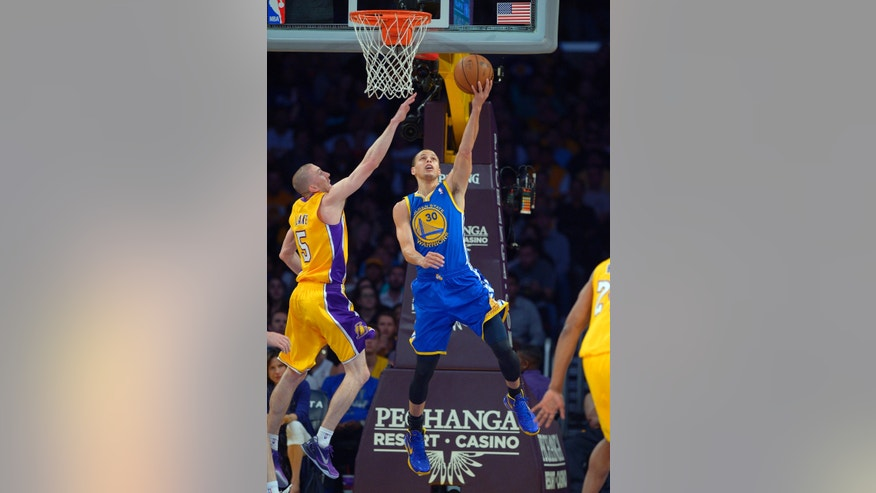 Golden State Warriors guard Stephen Curry, right, puts up a shot as Los Angeles Lakers guard Steve Blake, defends during the first half of their NBA basketball game, Friday, April 12, 2013, in Los Angeles. (AP Photo/Mark J. Terrill)