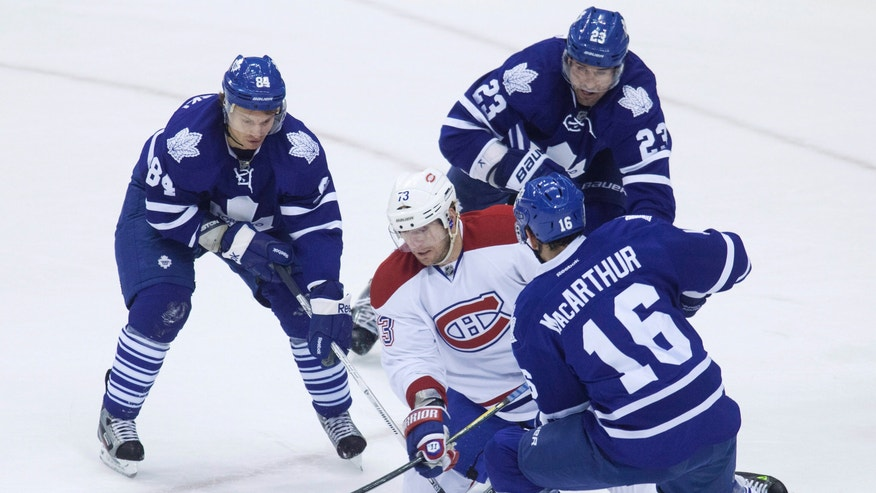 Montreal Canadiens' Michael Ryder is swarmed by Toronto Maple Leafs' Mikhail Grabovski, left, Ryan O'Byrne and Clarke MacArthur during first-period NHL hockey game action in Toronto, Saturday, April 13, 2013. (AP Photo/The Canadian Press, Jesse Johnston)