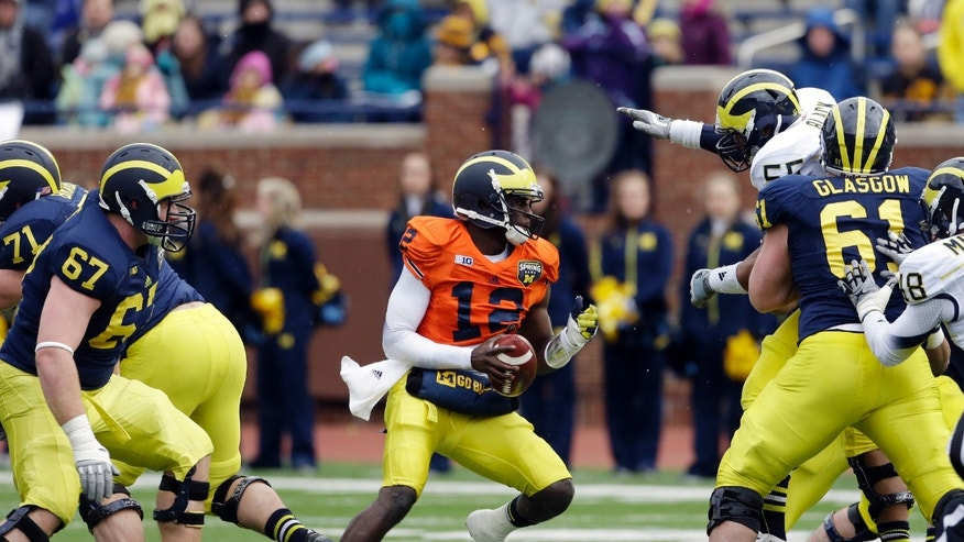 Michigan quarterback Devin Gardner looks for running room during an NCAA college football spring scrimmage, Saturday, April 13, 2013, in Ann Arbor, Mich. (AP Photo/Carlos Osorio)