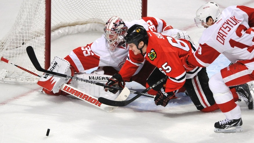 Chicago Blackhawks' Andrew Shaw (65) chases the puck against Detroit Red Wings' Pavel Datsyuk (13), of Russia, and goalie Jimmy Howard during the first period of an NHL hockey game in Chicago, Friday, April 12, 2013. (AP Photo/Paul Beaty)