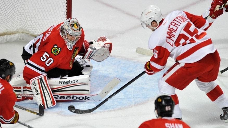 Detroit Red Wings' Cory Emmerton (25), scores a goal against Chicago Blackhawks goalie Corey Crawford (50) during the second period of an NHL hockey game in Chicago, Friday, April 12, 2013. (AP Photo/Paul Beaty)