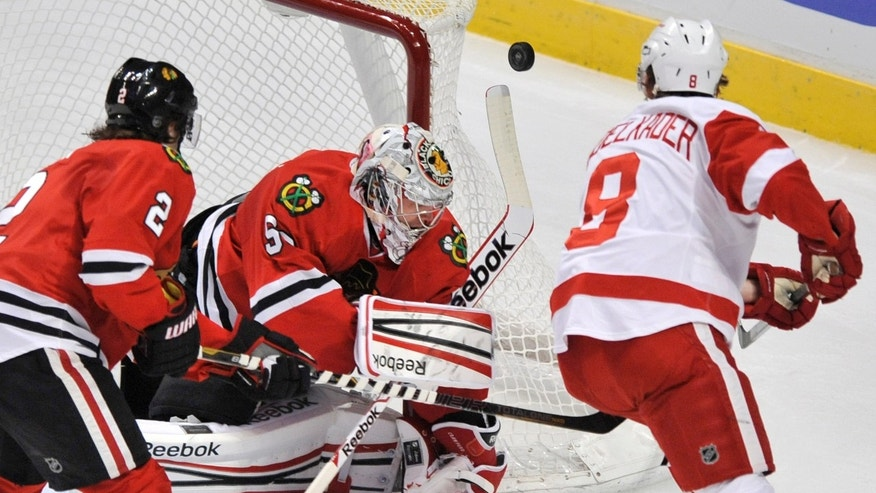 Chicago Blackhawks goalie Corey Crawford makes a save against Detroit Red Wings' Justin Abdelkader (8) while Blackhawks' Duncan Keith (2), looks on during the first period of an NHL hockey game in Chicago, Friday, April 12, 2013. (AP Photo/Paul Beaty)