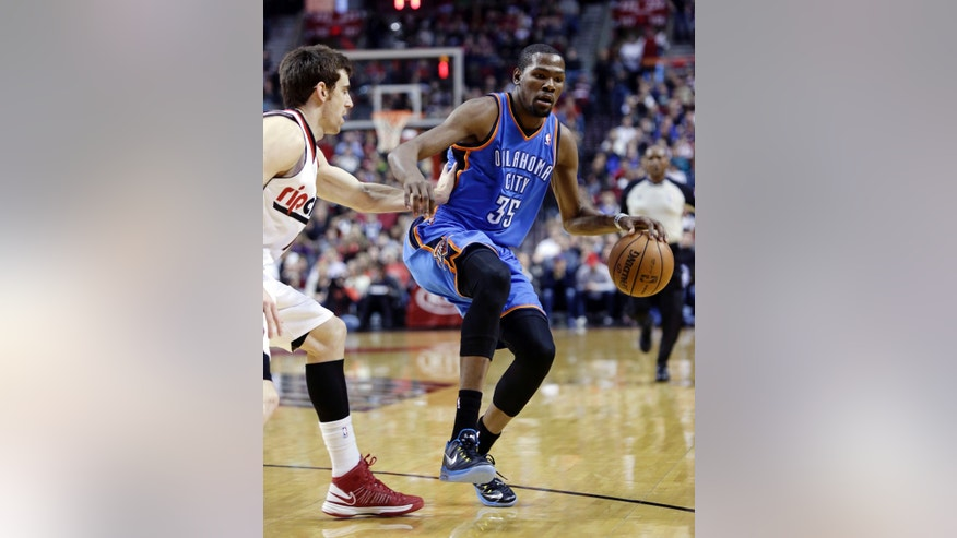 Oklahoma City Thunder forward Kevin Durant, right, dribbles against Portland Trail Blazers forward Victor Claver, from Spain, during the first quarter of an NBA basketball game in Portland, Ore., Friday, April 12, 2013. (AP Photo/Don Ryan)