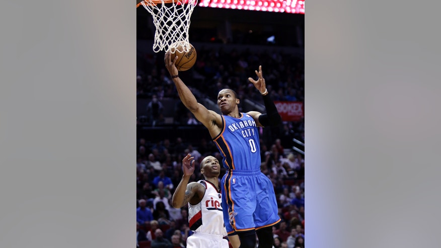 Oklahoma City Thunder guard Russell Westbrook, right, goes to the hoop past Portland Trail Blazers guard Damian Lillard during the first quarter of an NBA basketball game in Portland, Ore., Friday, April 12, 2013. (AP Photo/Don Ryan)