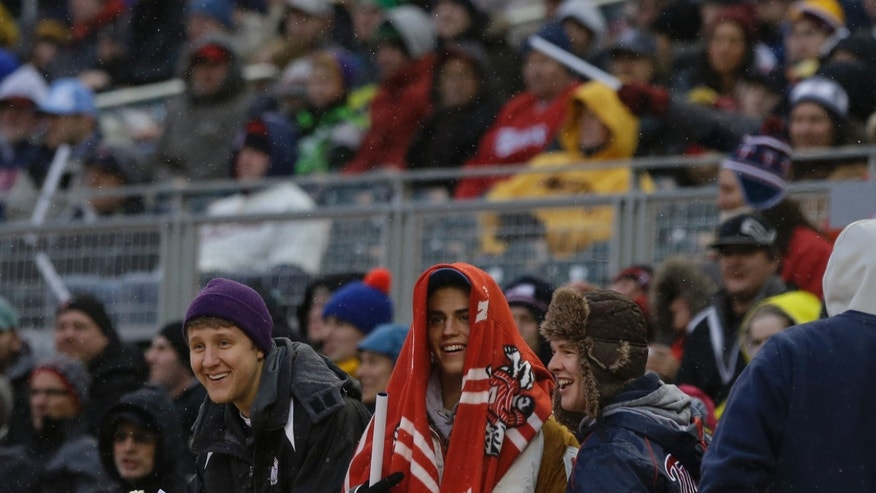 Warm clothes and even blankets amidst snow flakes were the order of the night for baseball fans during the Minnesota Twins and New York Mets baseball game, Friday, April 12, 2013, in Minneapolis. (AP Photo/Jim Mone)