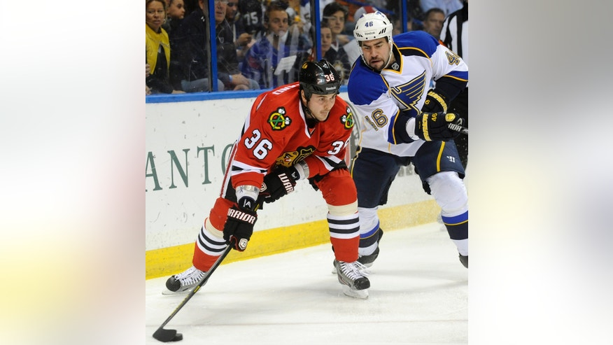 Chicago Blackhawks' Dave Bolland (36) gets the puck past St. Louis Blues' Roman Polak (46), of the Czech Republic, in the first period of an NHL hockey game on Sunday, April 14, 2013, in St. Louis. (AP Photo/Bill Boyce)