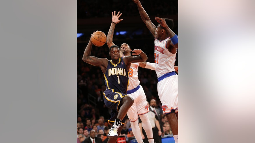 Indiana Pacers' Lance Stephenson, left, drives to the basket underneath New York Knicks' Iman Shumpert, right, and J.R. Smith during the first half of the NBA basketball game Sunday April 14, 2013 in New York.  (AP Photo/Seth Wenig)