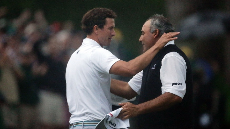 Adam Scott, left, of Australia, is congratulated by Angel Cabrera, of Argentina, after making a birdie putt on the second playoff hole to win the Masters golf tournament Sunday, April 14, 2013, in Augusta, Ga. (AP Photo/Charlie Riedel)