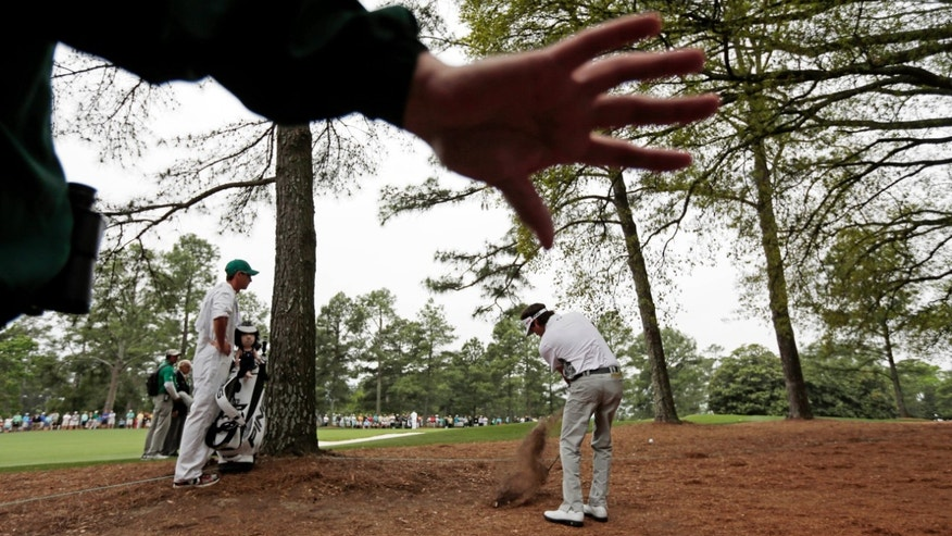 A course worker holds back the gallery as Bubba Watson hits out of the rough off the first fairway during the fourth round of the Masters golf tournament Sunday, April 14, 2013, in Augusta, Ga. (AP Photo/Charlie Riedel)
