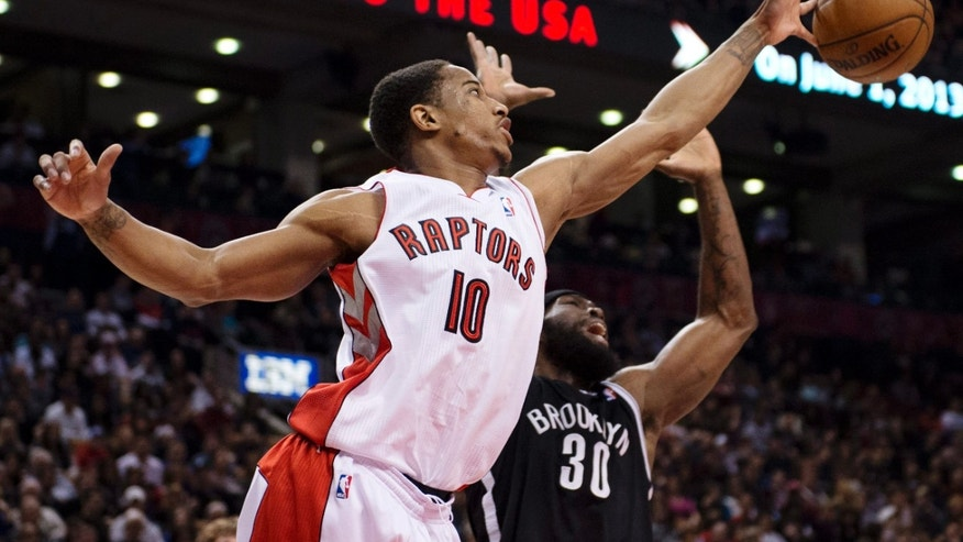Toronto Raptors guard DeMar DeRozan (10) reaches for a rebound against Brooklyn Nets forward Reggie Evans (30) during the first half of an NBA basketball game in Toronto, Sunday, April 14, 2013. (AP Photo/The Canadian Press, Frank Gunn)